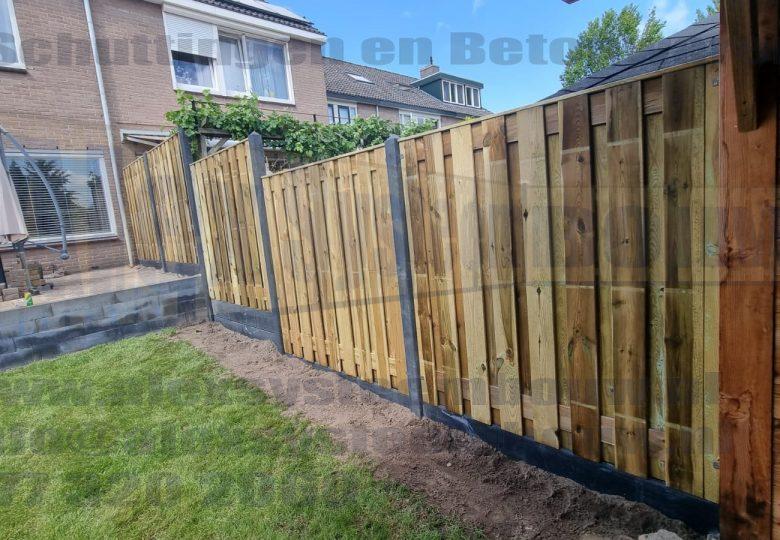 Een op maat gemaakte schutting die de verspringing kan overbruggen van het verhoogd terras.